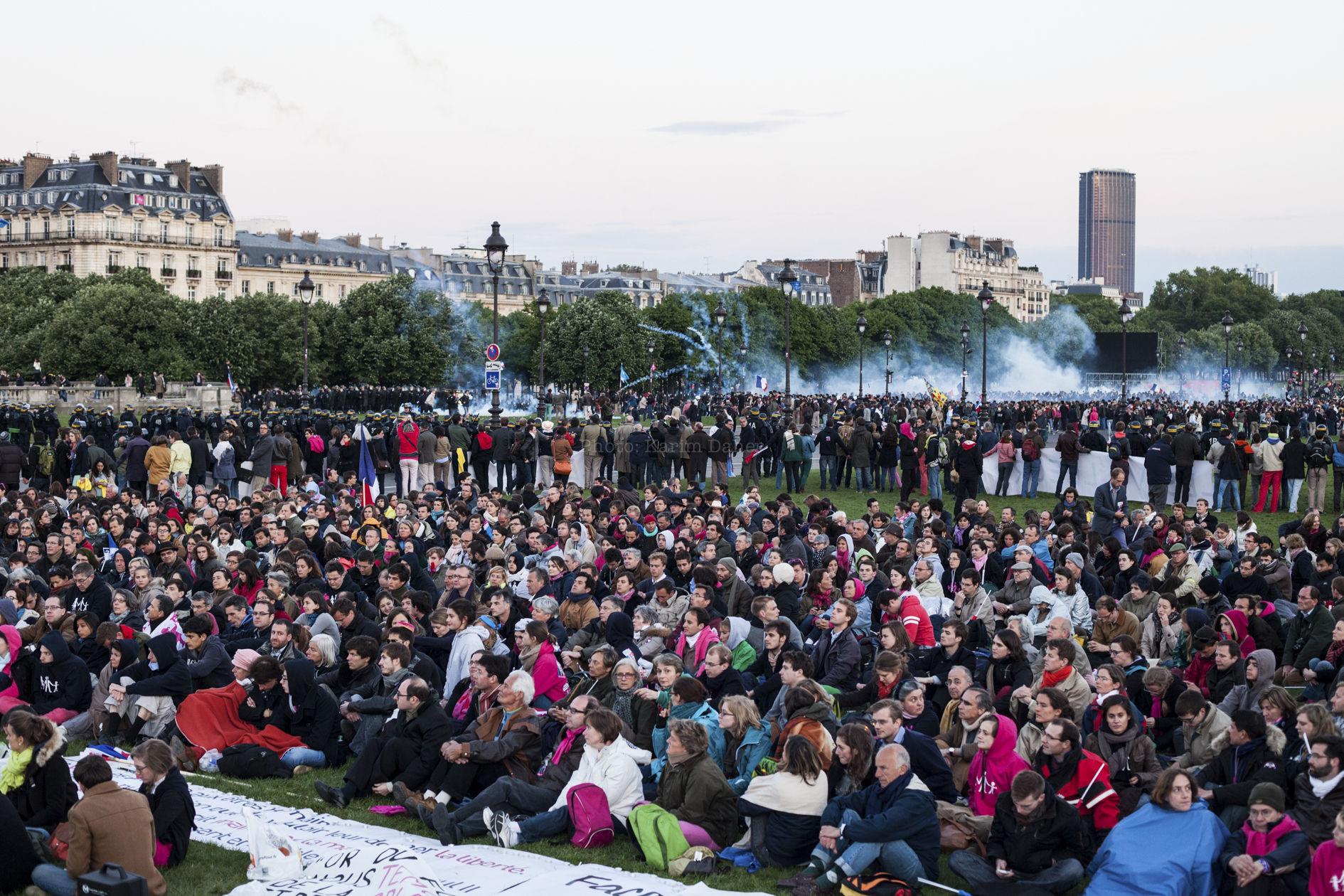 """Paris, Invalides, 26 Mai 2013. Après la dispersion de la manifestation contre la """"Loi Taubira"""", des """"veilleurs"""" (opposants pacifiques à la loi)  écoutent des orateurs alors que des affrontements ont lieu aux alentours, dans des nuages de gaz lacrymogène."""